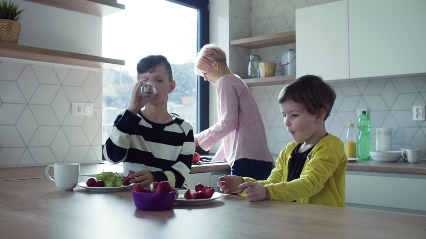 A young mother with two children eating fruit in a kitchen. | Shutterstock HD Video #1031600981
