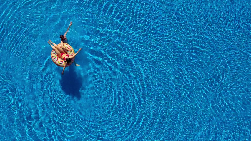 Aerial view of couple having fun in the pool, man is swimming and a woman is lying on an inflatable donut