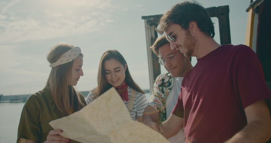Cheerful friends in trendy clothes standing near hippie van with dog using tourist map to visit local festival in the city, Cinematic Shot | Shutterstock HD Video #1031606984