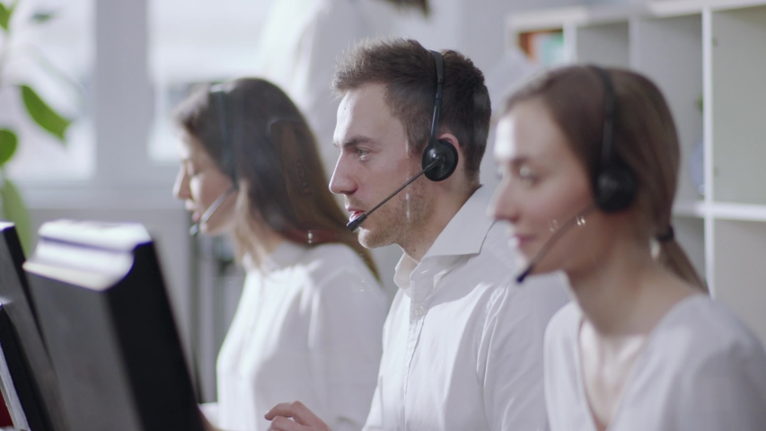 Business and technology concept - helpline operator with headphones in call centre working hard, then looks straight to camera and smiles happily. Politeness, good mood, positive emotions. Female