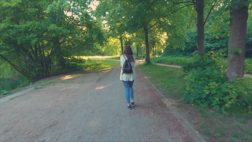 Young woman walking through a park with swinging arms at a sunny day | Shutterstock HD Video #1031617316