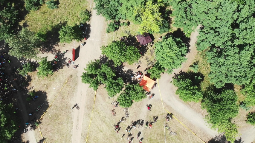 Drone flying around start area of bike race in green forest on sunny summer day | Shutterstock HD Video #1031632523