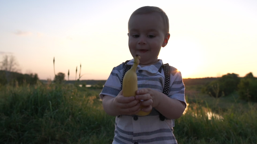 Joyful boy running with a banana on the summer field at sunset in slow motion | Shutterstock HD Video #1031640536