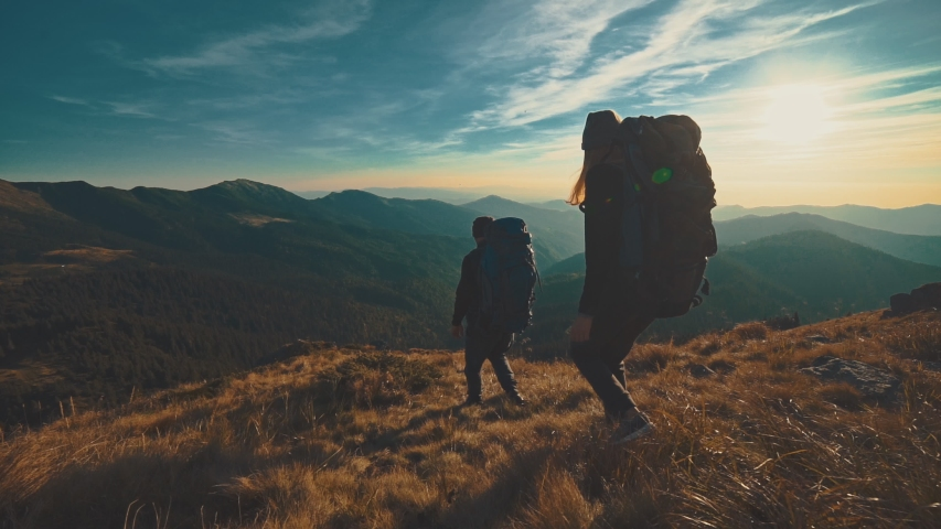 The man and woman walking in the mountain on the sunset background. slow motion | Shutterstock HD Video #1031661170