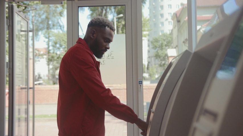 Serious handsome young man inserting credit card into bancomat entering a pin to receive money. African guy withdrawing money from cash dispenser in a bank. Royalty-Free Stock Footage #1031664641