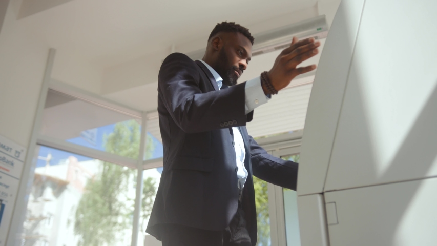 Annoyed bank client in suit in trouble with credit card withdrawal. Shocked young african american businessman standing under money rain inside the modern bank. Royalty-Free Stock Footage #1031664656