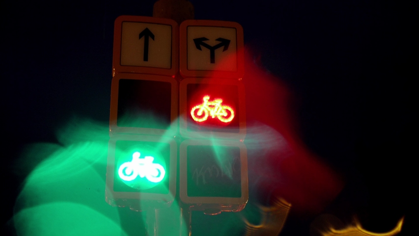 Abstract blurred lights of traffic light in the city, creative reflections and bokeh of the lights. Green and red colour in the evening. Urban area, bicycle road traffic light. Bike icon lighted.   Shutterstock HD Video #1031668817
