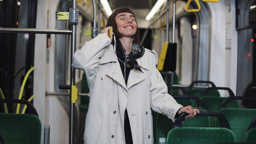 Portrait of young woman wearing in coat with headphones listening to music and funny dancing in public transport. He holds the handrail. | Shutterstock HD Video #1031672564