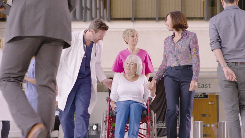 4K Caring medical staff assisting patient in a wheelchair in busy modern hospital | Shutterstock HD Video #10316753