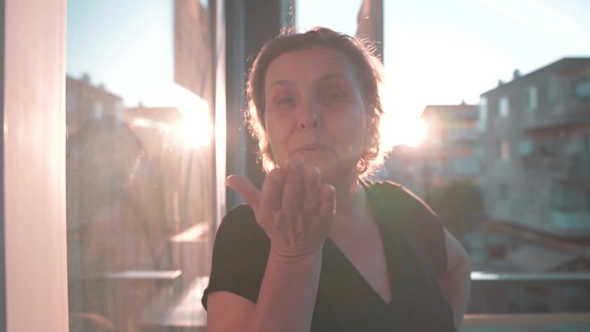 Old woman is sending, blowing kiss on balcony with sun light, glare. Happy aged retired mother | Shutterstock HD Video #1031682014