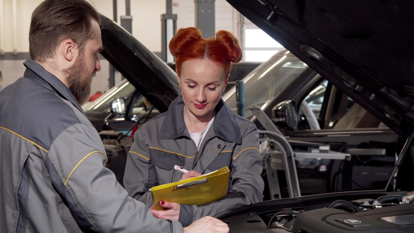 Beautiful female mechanic and her male colleague examining engine of a car Royalty-Free Stock Footage #1031695934