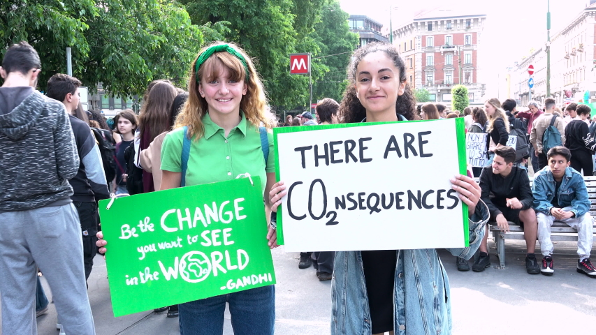 MILAN, ITALY - MAY 24, 2019: Happy girls demonstrating at global strike for climate. Students skipping school with picket signs, smiling young women at Friday for future event, ecologist movement