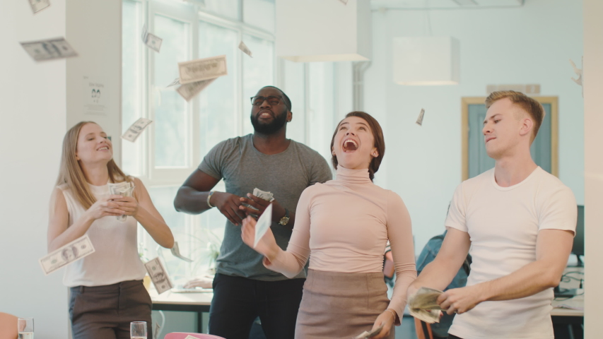 Happy people throwing away dollar banknote at coworking. Young people making rain with money at open space. Dollar banknote flying in air in office. Smiling team dancing with money at open space.