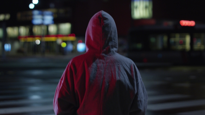 Shot from behind of confident and ambitious  walking  on the night street with hoodie. slow motion. Shot on RED Dragon. | Shutterstock HD Video #1031709821