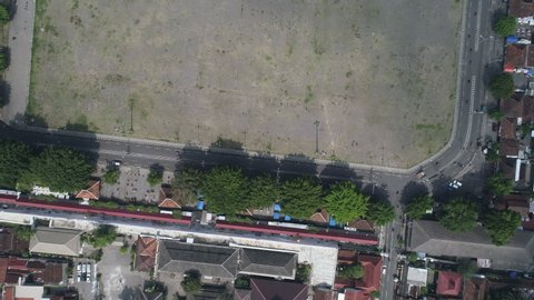 Approaching top view aerial footage of Yogyakarta North Square and traffic situation, known as Alun-Alun Utara in Yogyakarta city. Showing busy traffic, house and office building neighborhood top view