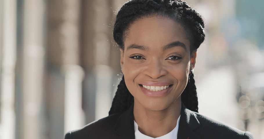 Portrait of stylish African American business woman standing on the old street background. She looking at the camera and smiling. Black Stylish. Dreadlocks. Afro Hairstyle.   Shutterstock HD Video #1031729723