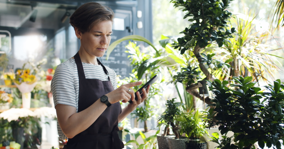 Slow motion of female florist in apron using tablet at work counting plants touching screen writing down information. Small business and technology concept.
