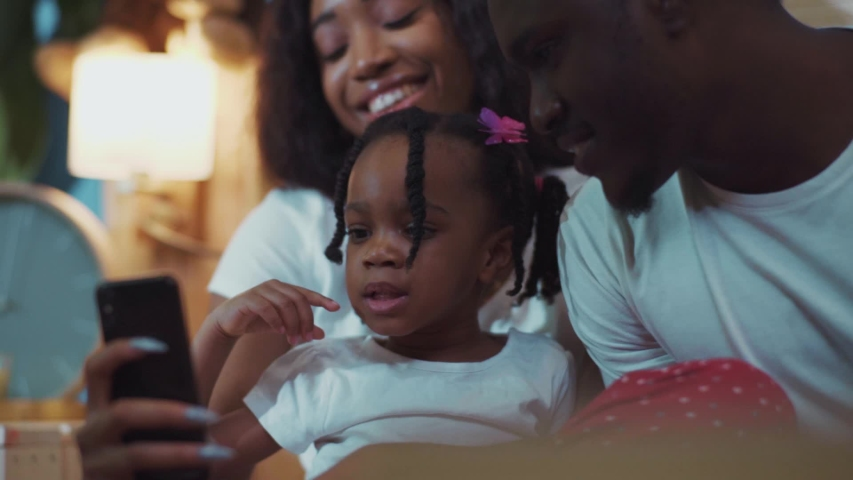 Happy african family with a little cute daughter having fun using smartphone indoors. Portrait of lovely smiling girl lwith braids laughing and watching fun videos with parents on couch.