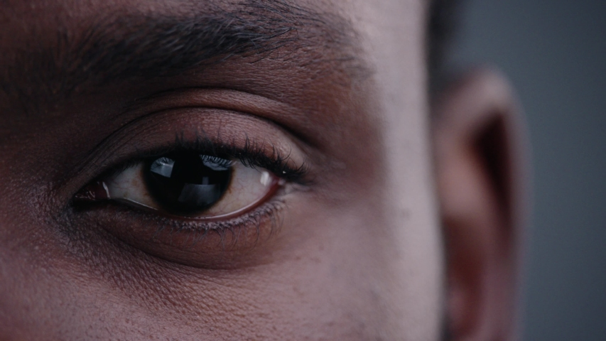 Highly detailed portrait of young mature man staring at camera. Close-up cropped view of beautiful african black man eye on grey background.