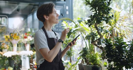 Young entrepreneur touching tablet screen looking at flowers in florist's shop enjoying nature and modern technology. People, entrepreneurship and business concept.