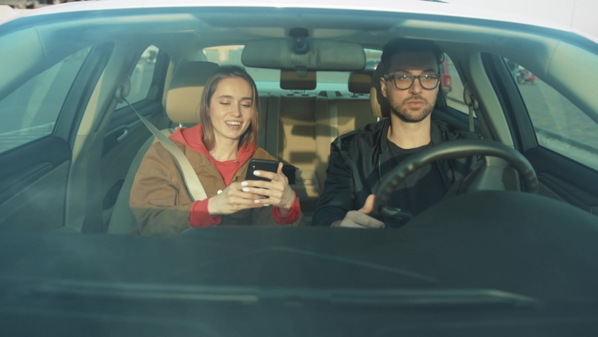 Man and woman sitting in car, talking and laughing. Girl and boyfriend spending time together, having fun.Travelling. Car's interior. | Shutterstock HD Video #1031742617