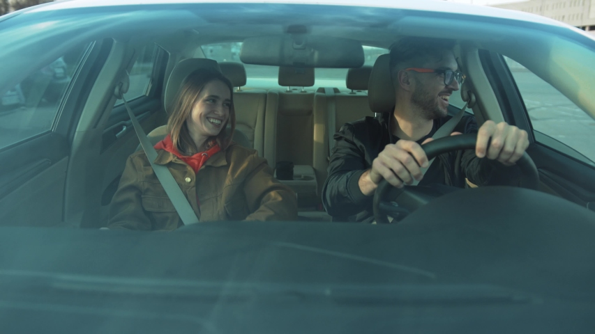 Cheerful Caucasian couple in love sitting in car, girl moving in rhythm. Young people having fun together. Good mood. Enjoy. Car's interior. | Shutterstock HD Video #1031742713