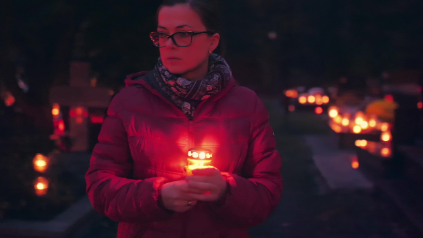 Woman visiting graveyard at night holding burning candle