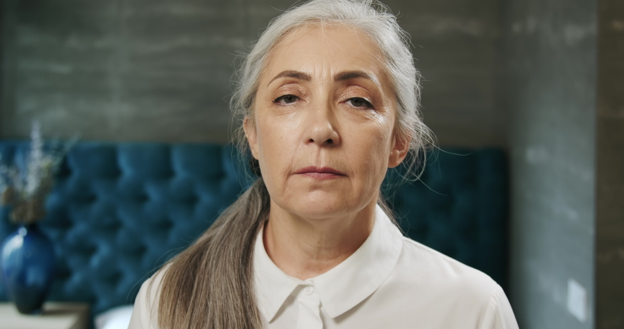 Beautiful senior lady dressed in white blouse looking to camera and smiling, social security for retirees | Shutterstock HD Video #1031758013