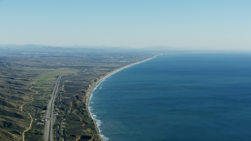 Aerial view of Pacific ocean coastline sweeping beaches Los Angeles to San Diego Highway US1 Toll road Amtrak Railroad California America RED WEAPON