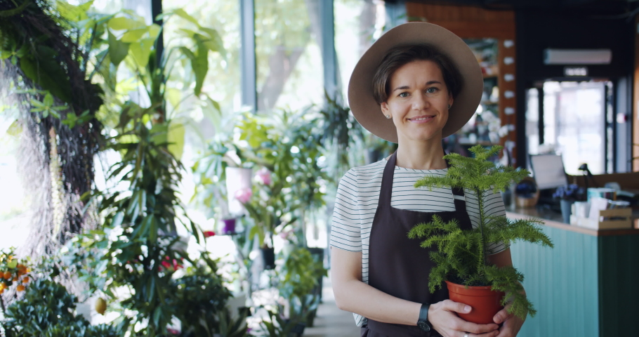 Slow motion portrait of cute young lady in apron and hat holding potted plant in florist's store smiling looking at camera. Business, people and houseplants concept.