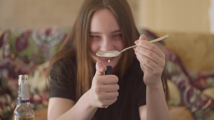 Young smiling woman with long hair warming a spoon with heroin on a lighter fire close-up. Drug use, addiction. Troubled teens. Drug addiction. | Shutterstock HD Video #1031766614