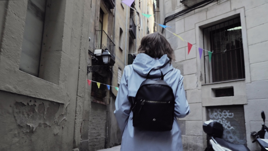 Back view of a girl with backpack walking through tight street. #1031770715