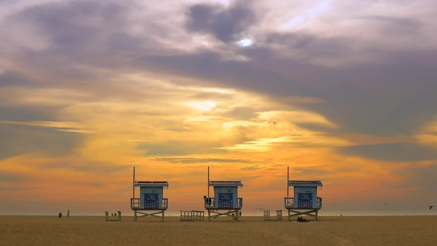 VENICE BEACH, SANTA MONICA, LOS ANGELES, CA - Jun 2019. Silhouettes of lifeguard wooden houses in front of the ocean. Birds and people by the seawater.