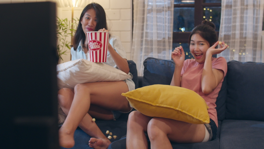 Lesbian lgbt women couple watching movie at home, Asian female lover eating popcorn scary and shock while looking horror film together on sofa in living room in night concept. Slow motion shot. | Shutterstock HD Video #1031771648