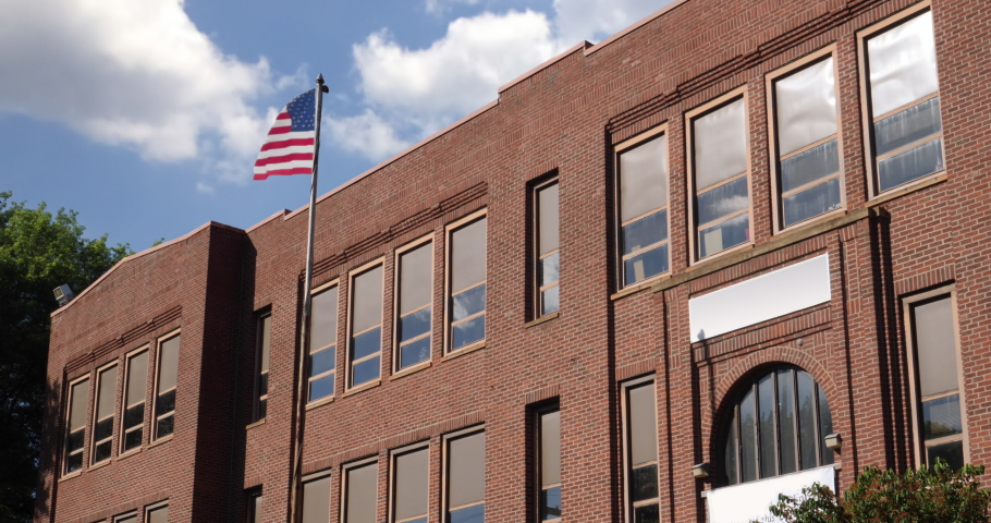 A daytime summer establishing shot of a typical two-story red brick school building in a small midwestern town. Low angle. American flag waving on flagpole in front.