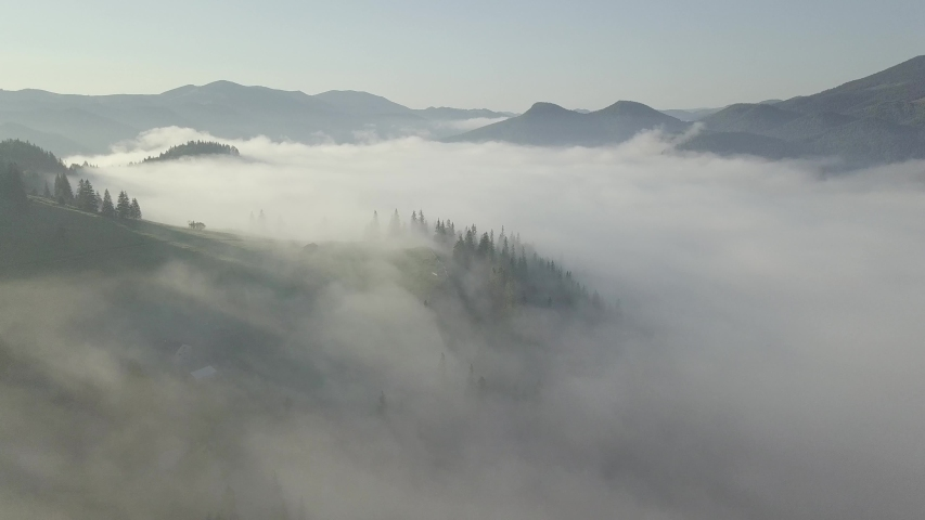 Surreal sunrise in the Smoky mountain skies. Drone video lifting up and panning to reveal the sunrise through the clouds in the Blue Ridge Great Smoky Mountains of Tennessee #1031808299