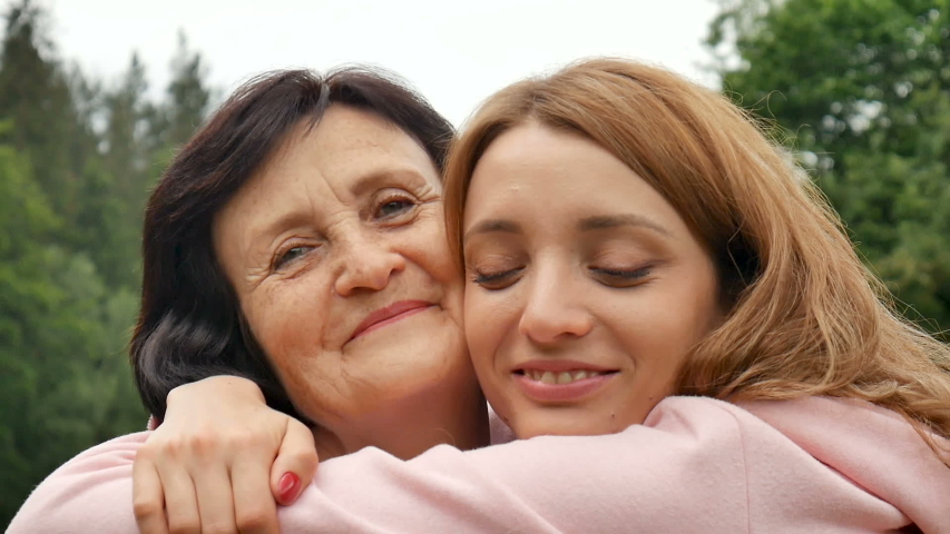 Outdoor close up portrait of smiling happy caucasian senior mother with her adult daughter hugging and looking at the camera. Adult daughter kisses mother, mother's day
