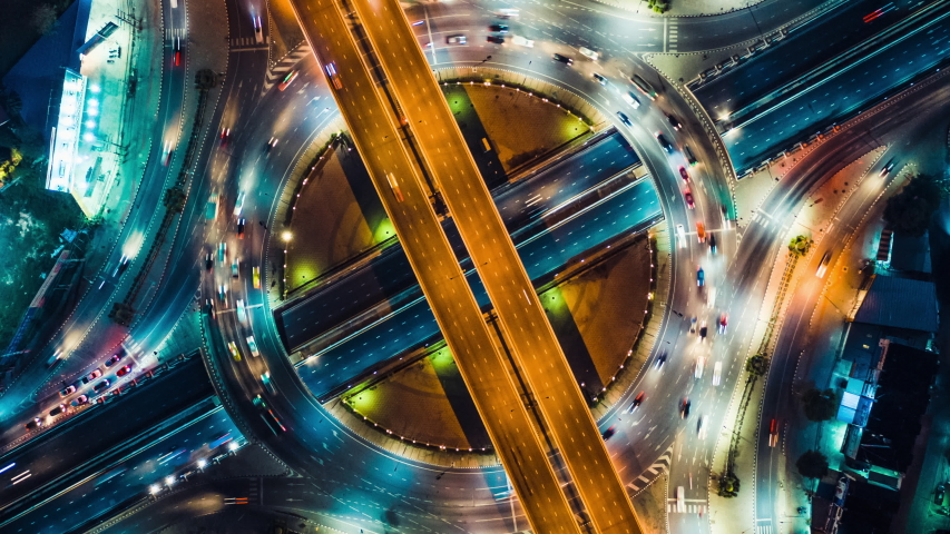 Beautiful top view time-lapse of car traffic at roundabout lane and buildings. 4K drone aerial zoom out. Urban cityscape concept or abstract of advanced innovation, financial technology, energy power Royalty-Free Stock Footage #1031822039