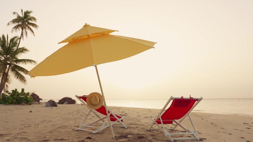 Beach umbrella and beach chair on the palms island isolated. The sun sunset background. Dominican Republic Punta Cana Palms island beach. Caribbean sea nature sunset. Sun umbrella over beach loungers | Shutterstock HD Video #1031826998