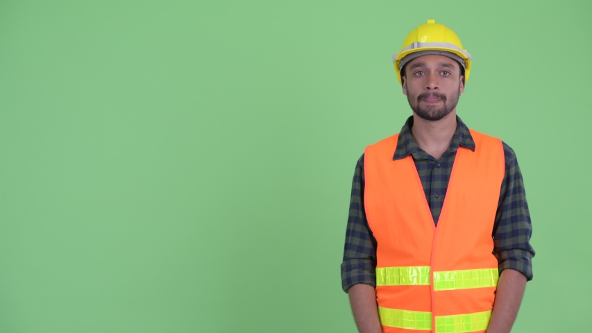 Happy young bearded Persian man construction worker snapping fingers and giving thumbs up
