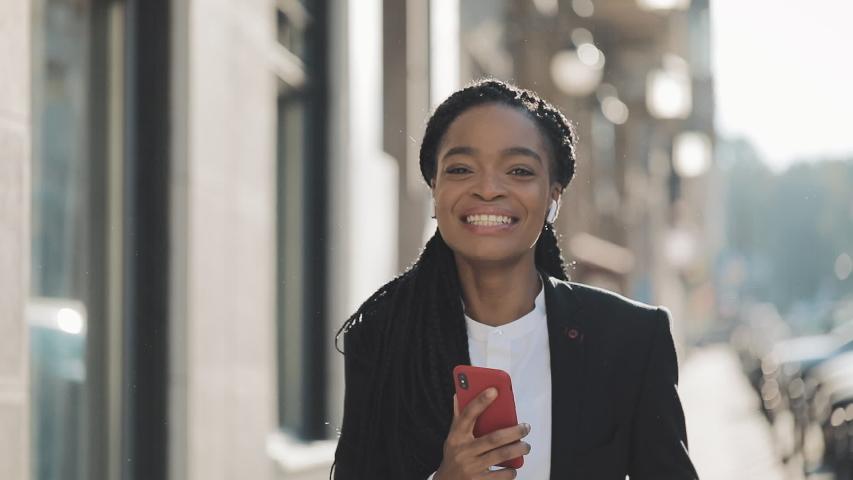 Young happy African American businesswoman in earphones walking the city street while listening to the music on the smartphone and dancing. Outdoor. | Shutterstock HD Video #1031829323