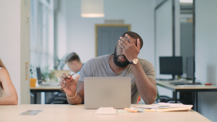 Upset man reading bad news on laptop computer at coworking space. Serious afro man stressed at office workplace. African male professional making mistake working on laptop in office. Royalty-Free Stock Footage #1031832491
