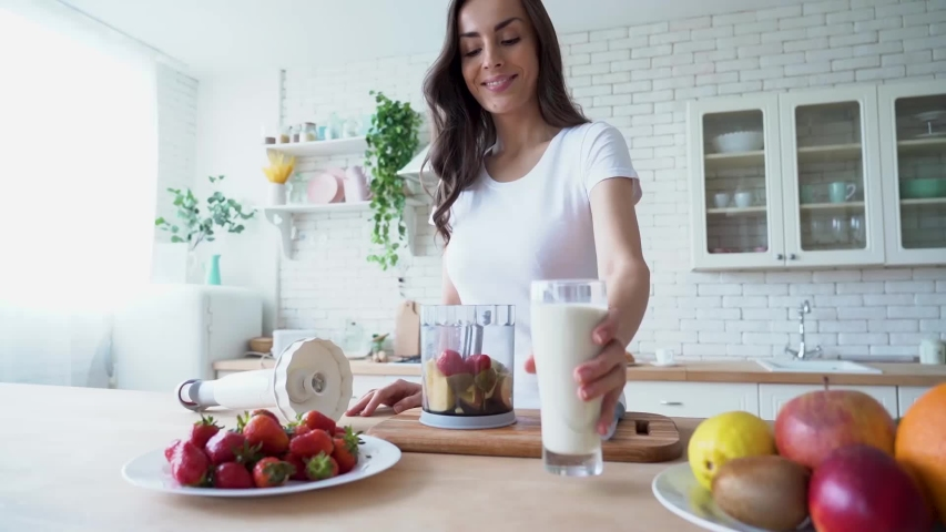 Healthy vegan smoothie with fruits. Beautiful happy young woman in casual home clothes is preparing fitness cocktail with vegetable milk and different season fruits on the kitchen at home. Sporty meal