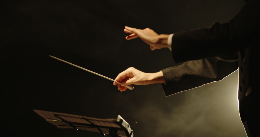 Close up shot of hands of symphony orchesra conductor directing music by waving his baton. Studio shot on black background 4k footage