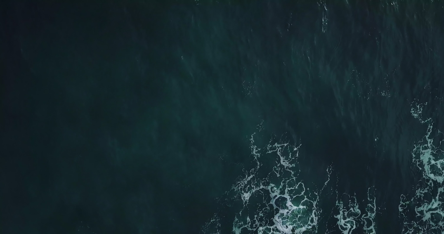 Timelapse. Aerial top view waves break on rocks in a blue ocean. Sea waves on beautiful beach aerial view drone 4k shot. Bird's eye view of ocean waves crashing against an empty stone from above. Royalty-Free Stock Footage #1031874680