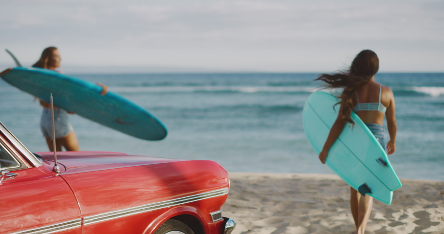 Young attractive women at the beach with vintage beach cruiser car, getting ready to surf at sunset, island beach lifestyle