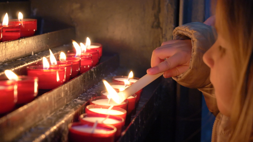 Detail of a beautiful blonde little girl lighting candles carefully in a church and then blowing them. Tongeren. Belgium. Flat plane Royalty-Free Stock Footage #1031881439