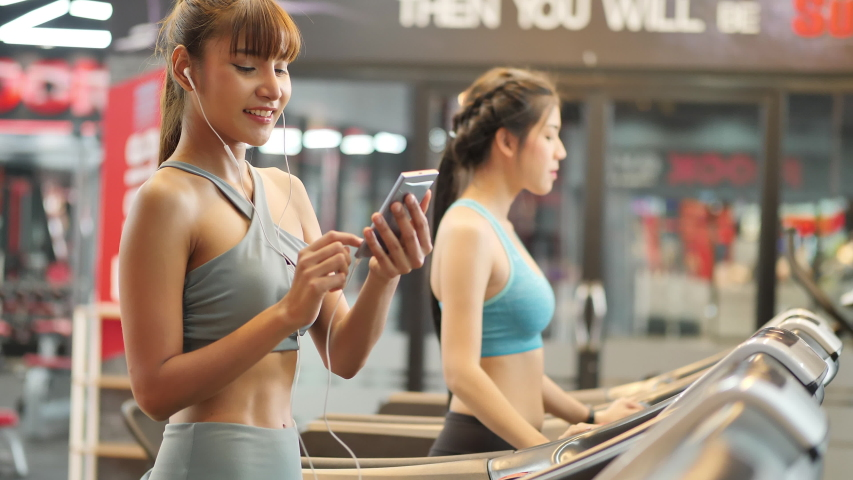 Young beautiful woman asian running on a treadmill at gym listening to music on smartphone via sport earphone. Fitness and healthy lifestyle concept. Side view of girl in sportswear. Slow motion | Shutterstock HD Video #1031891546