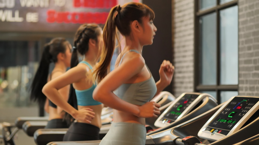 Group Young beautiful woman asian running on a treadmill at gym. Fitness and healthy lifestyle concept. Side view of girl in sportswear jogging exercise. Slow motion