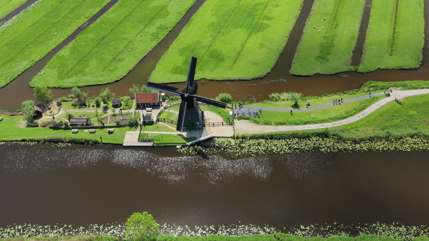 Aerial view of historic windmill in Kinderdijk village, famous Dutch tourist destination and UNESCO World Heritage Site - South Holland, Netherlands, landscape panorama of Europe from above Royalty-Free Stock Footage #1031905955